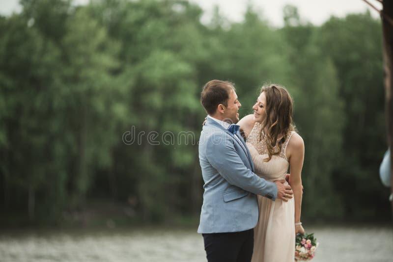 Sposa di trasporto dello sposo vicino al lago ed alla foresta immagine stock libera da diritti