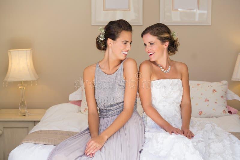 Sposa e damigella d'onore felici mentre sedendosi sul letto a casa immagini stock libere da diritti