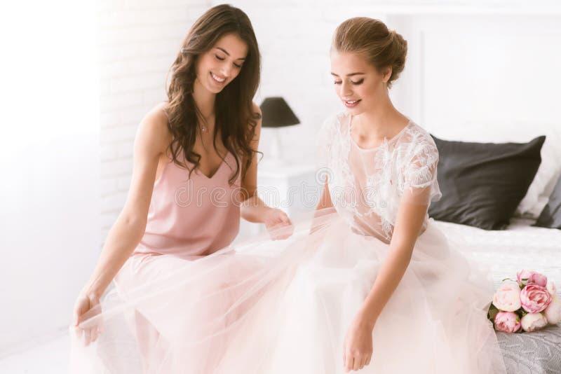 Sposa e damigella d'onore sorridenti che si siedono sul letto immagine stock