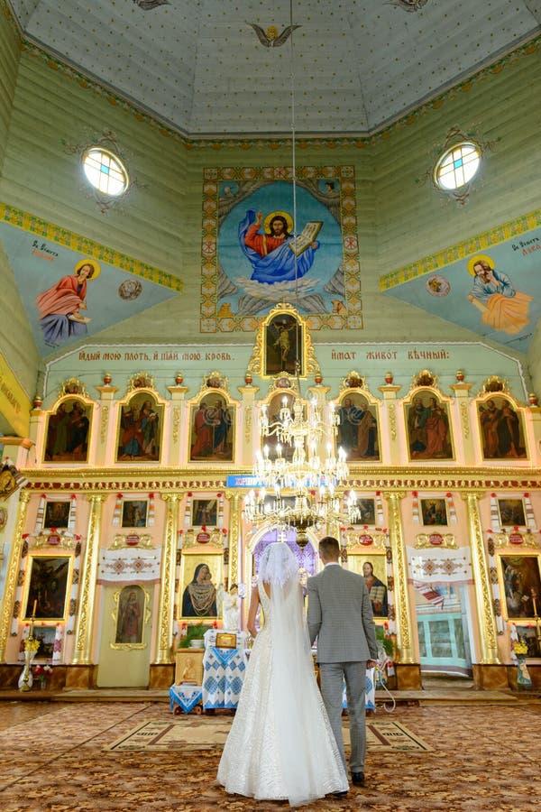 Sposa e sposo alla chiesa durante la cerimonia di nozze fotografia stock