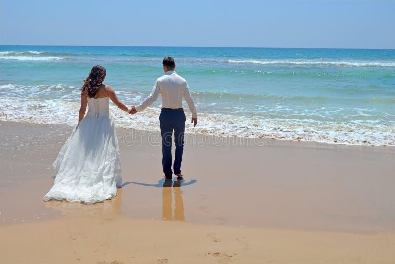 Sposa e sposo castana dai capelli lunghi in un vestito le persone appena sposate che si tengono per mano, vanno alla sabbia nell' immagini stock