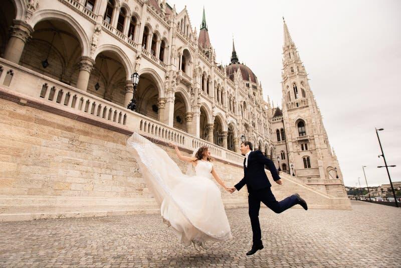 Sposa e sposo che abbracciano nella vecchia via della citt? La coppia di nozze cammina a Budapest vicino alla sede del parlamento fotografie stock