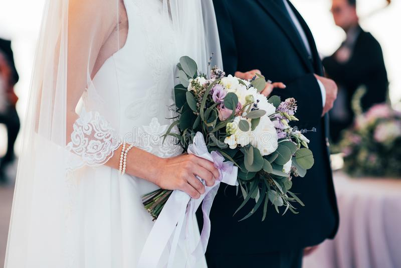Sposa e sposo che camminano insieme tenendo le loro mani immagini stock