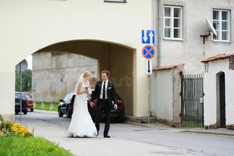 Sposa e sposo che camminano in una città fotografia stock