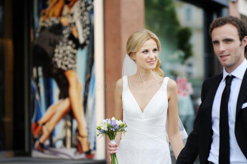 Sposa e sposo che camminano in una città immagini stock