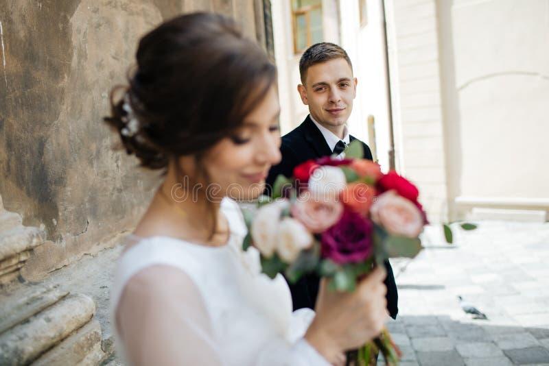 Sposa e sposo che camminano in una città soleggiata alle grandi costruzioni immagini stock libere da diritti