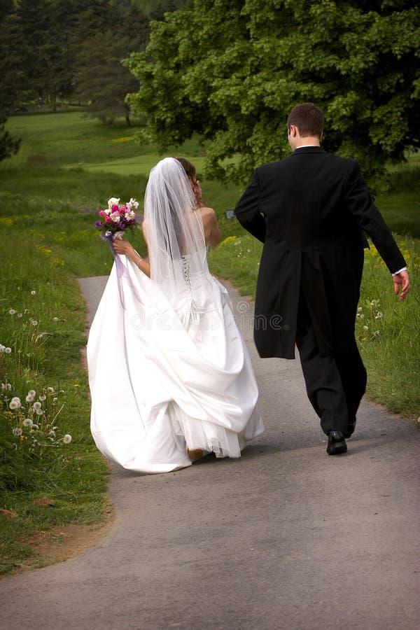 Sposa e sposo che camminano via fotografia stock