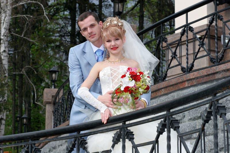 Sposa e sposo che esaminano in qualche luogo e sorridere immagine stock