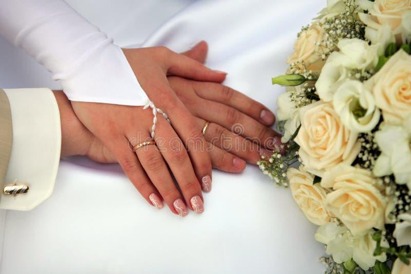 Sposa e sposo che mostrano gli anelli di cerimonia nuziale immagine stock