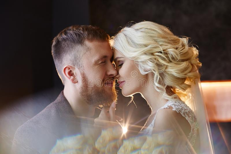 Sposa e sposo che non abbracciano e che baciano sul loro giorno delle nozze fuoco Creare una nuova famiglia, una coppia felice ne fotografie stock