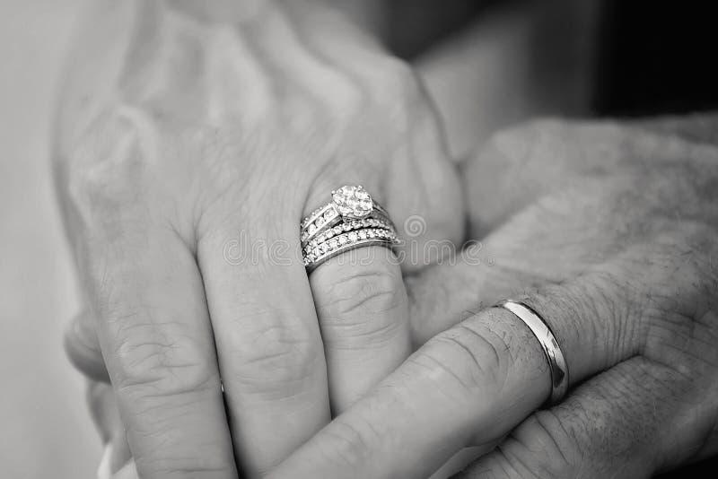 Sposa e sposo che ostentano i loro anelli fotografia stock