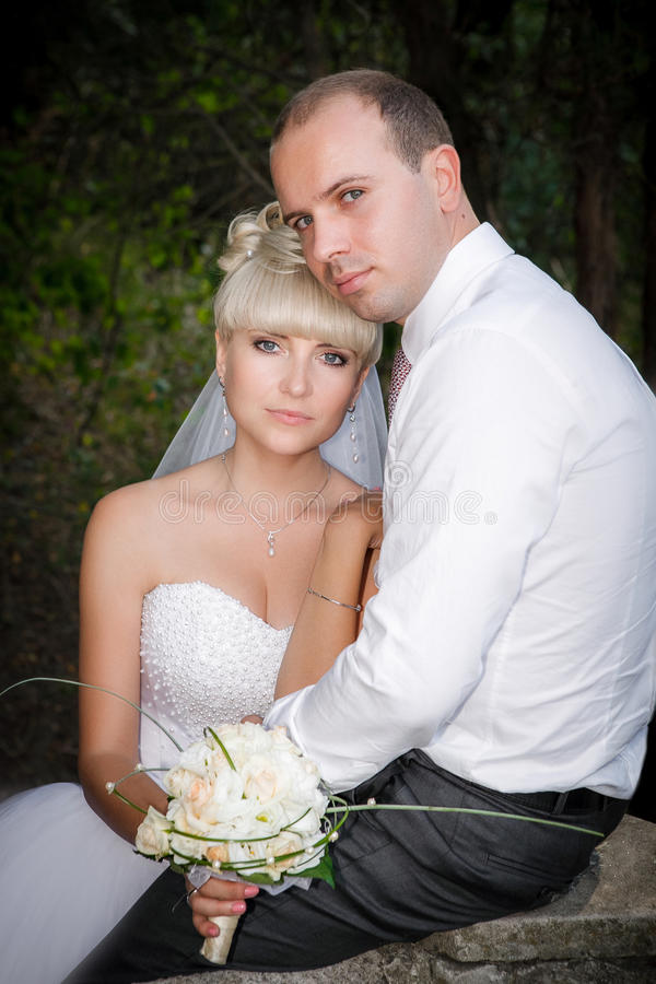Sposa e sposo che posano insieme all'aperto immagine stock