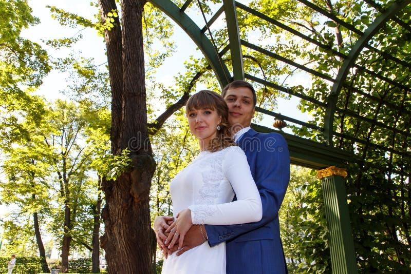 Sposa e sposo che si abbracciano delicatamente durante la passeggiata nella s immagine stock