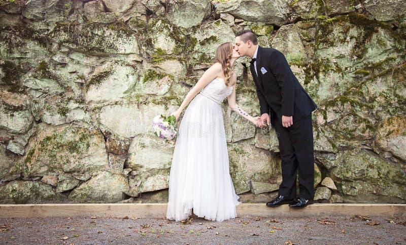 Sposa e sposo che si tengono per mano baciare davanti alla parete della roccia immagini stock
