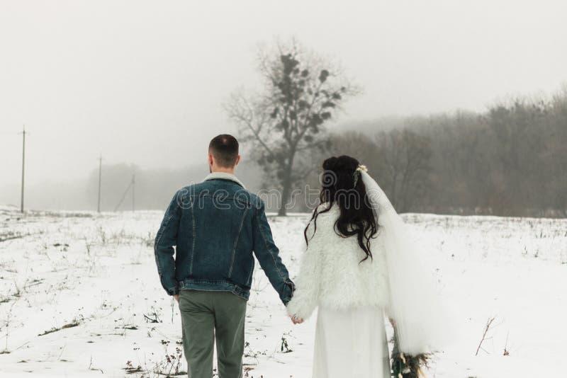 Sposa e sposo che si tengono per mano camminata giù il percorso dopo la cerimonia fotografie stock