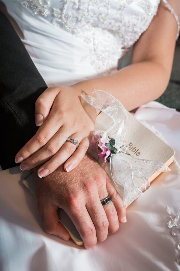 Sposa e sposo che si tengono per mano mostra gli anelli e della bibbia immagine stock libera da diritti