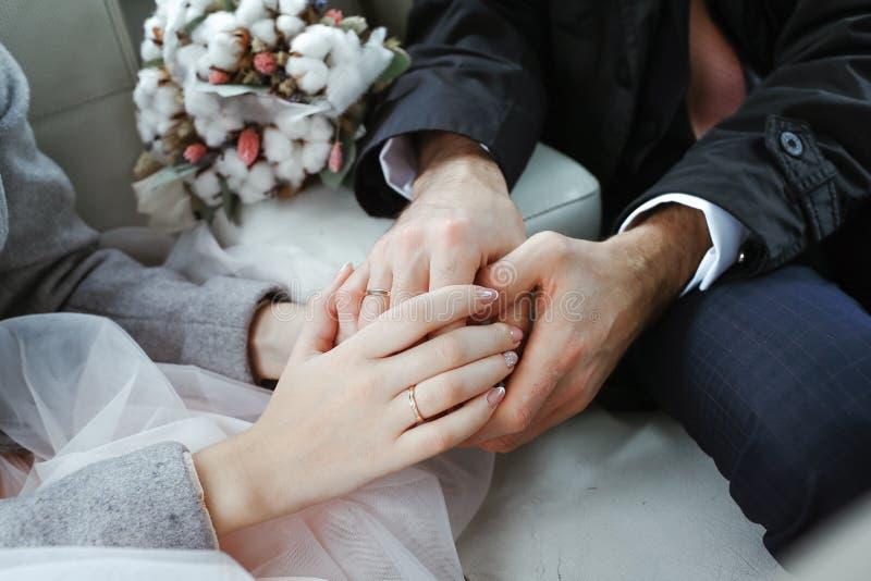 Sposa e sposo che si tengono per mano nell'automobile immagini stock
