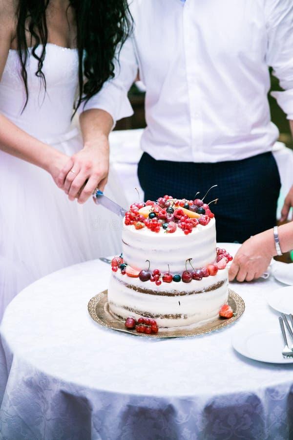 Sposa e sposo che tagliano torta nunziale bianca sulla tavola immagini stock libere da diritti
