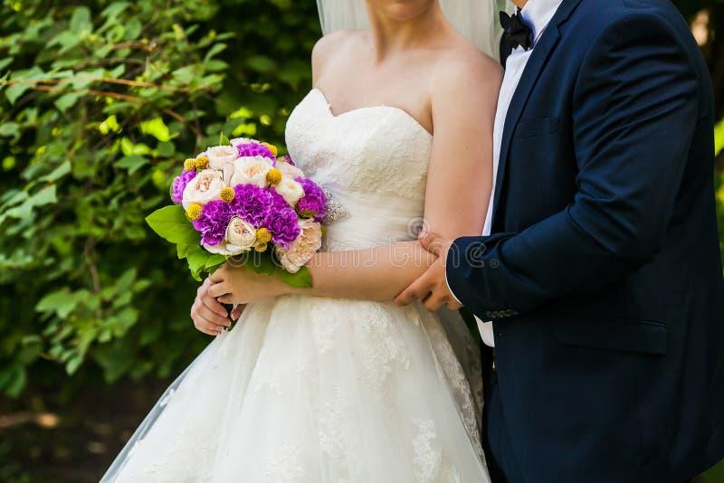 Sposa e sposo che tengono fine nuziale del mazzo su immagini stock