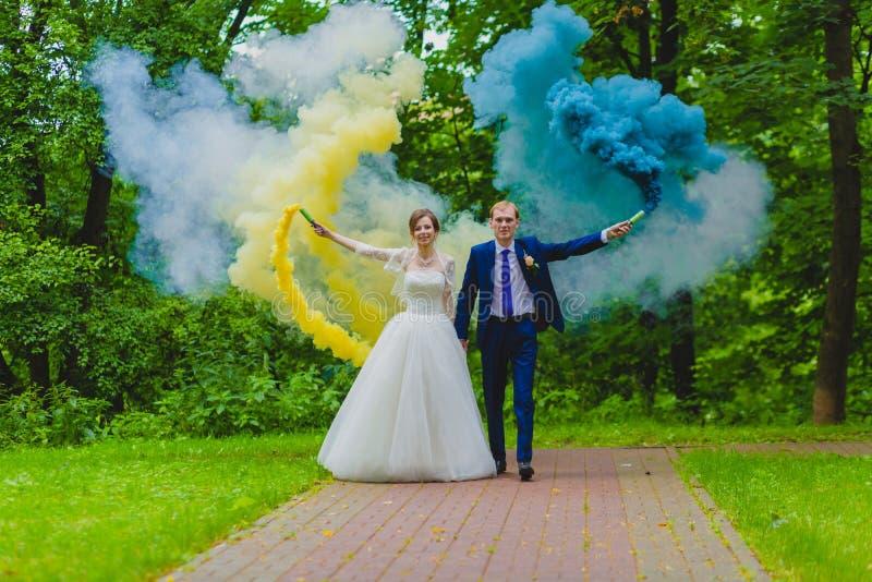 Sposa e sposo con le bombe fumogene variopinte immagini stock libere da diritti