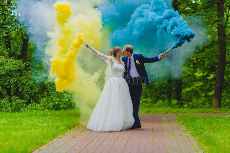 Sposa e sposo con le bombe fumogene variopinte fotografie stock