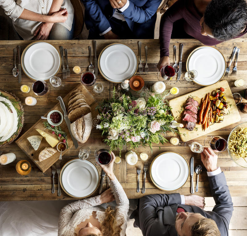 Sposa e sposo Eating con gli amici al ricevimento nuziale fotografia stock