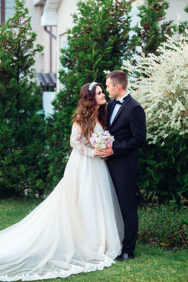 Sposa e sposo felici in parco sul loro giorno delle nozze fotografia stock libera da diritti