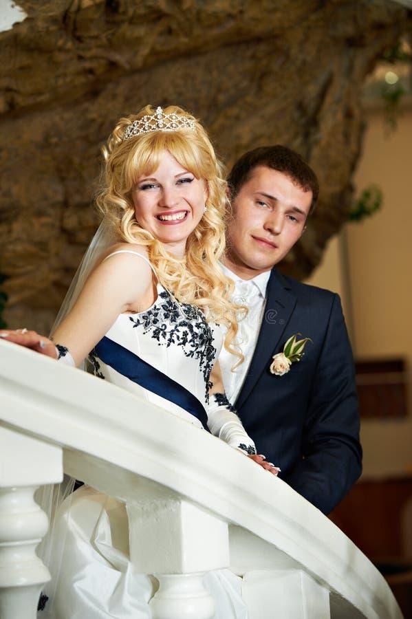 Sposa e sposo felici su una scaletta bianca immagini stock libere da diritti