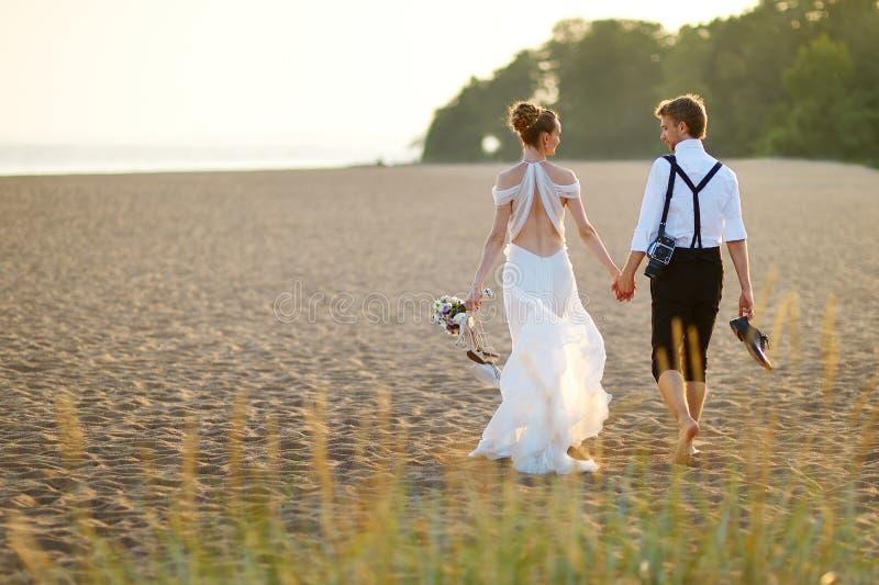 Sposa e sposo su una spiaggia al tramonto fotografia stock