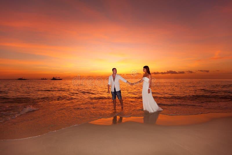 Sposa e sposo su una spiaggia tropicale con il tramonto nel backg immagine stock
