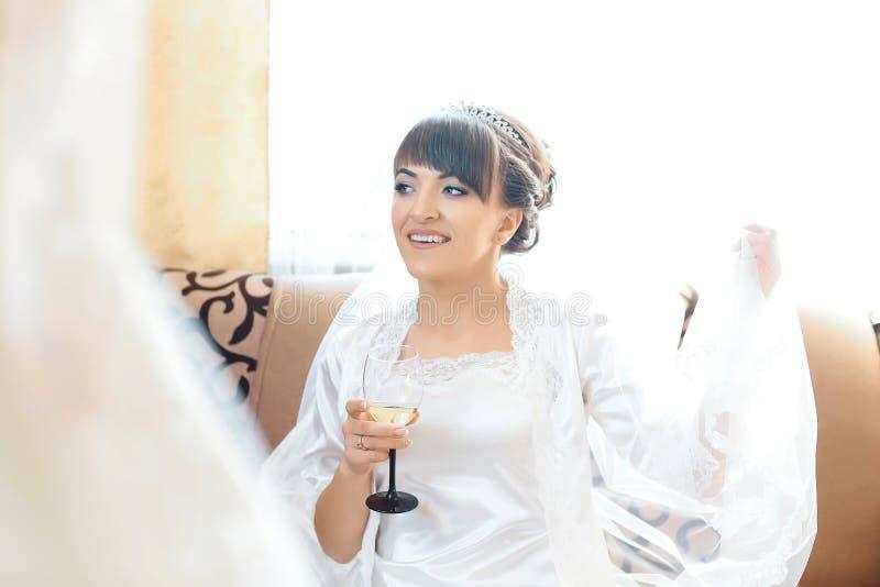 Sposa elegante in bicchiere di vino della tenuta dell'accappatoio Nozze, preparazione mattina di giorno delle nozze della sposa fotografia stock
