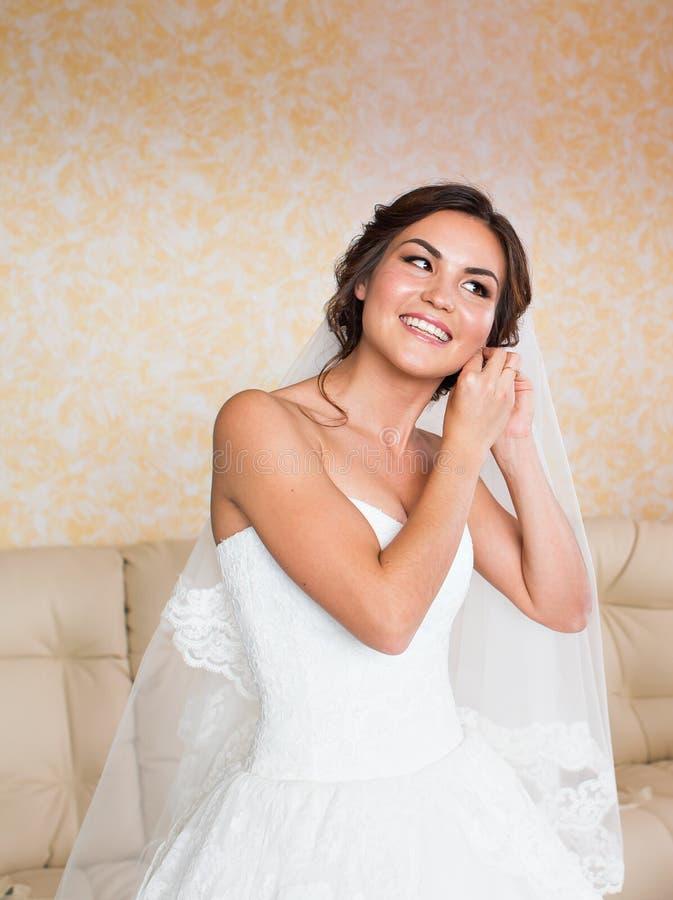 Sposa elegante che mette sugli orecchini, preparanti per le nozze fotografie stock