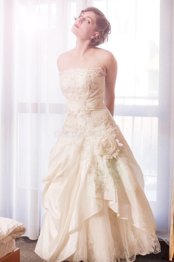 Sposa elegante che posa davanti alla finestra immagine stock