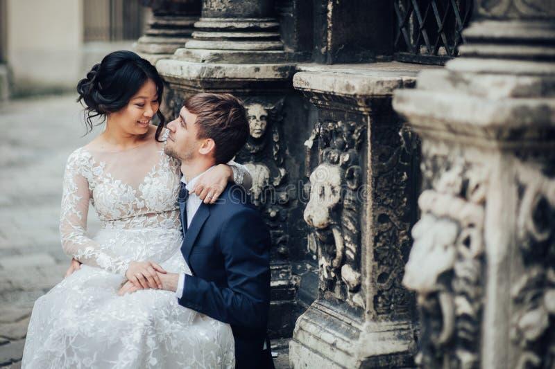 Sposa elegante con lo sposo che cammina vicino alla vecchia cattedrale cattolica immagine stock