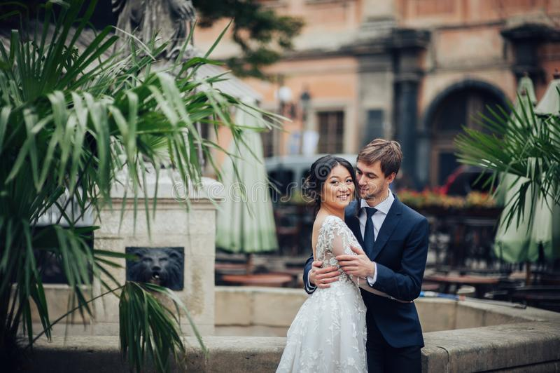 Sposa elegante con lo sposo che cammina vicino alla vecchia cattedrale cattolica fotografie stock