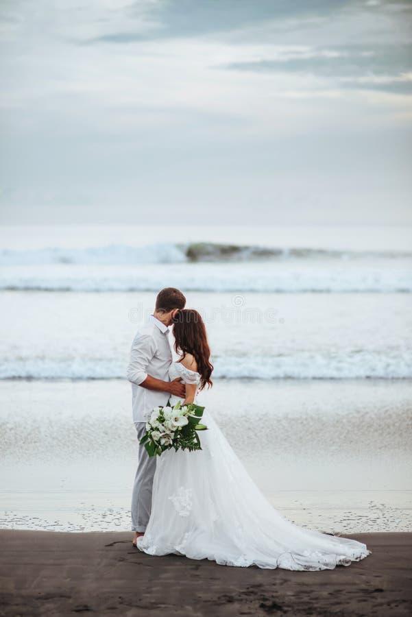 Sposa elegante e sposo splendidi che camminano sulla spiaggia dell'oceano durante il tempo di tramonto fotografia stock