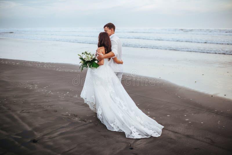 Sposa elegante e sposo splendidi che camminano sulla spiaggia dell'oceano durante il tempo di tramonto fotografie stock