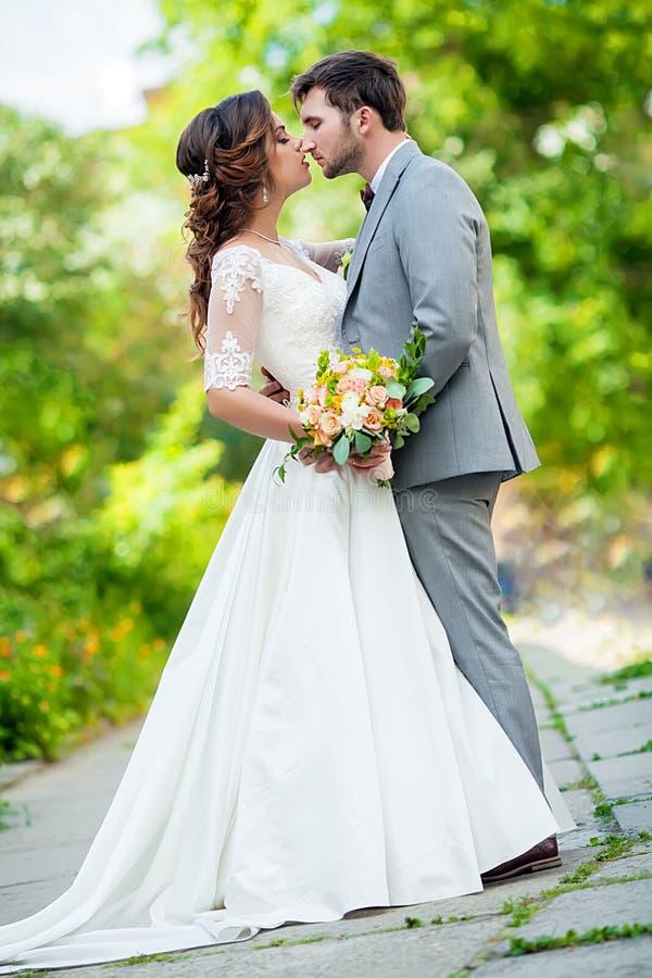 Sposa europea e sposo che baciano nel parco fotografia stock