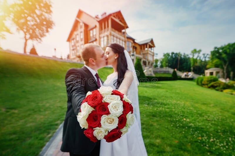 Sposa europea e sposo che baciano nel parco vicino alla casa immagini stock libere da diritti