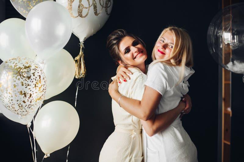 Sposa felice che abbraccia con la damigella d'onore e che esamina macchina fotografica immagine stock libera da diritti