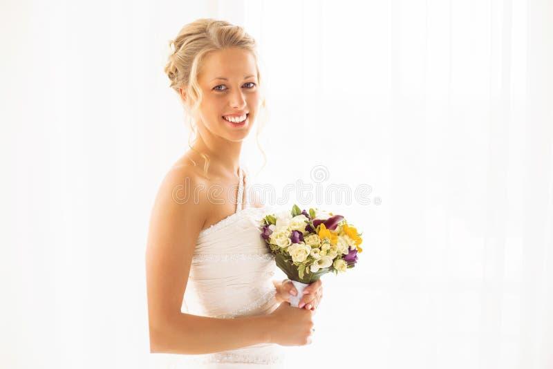 Sposa felice che tiene i suoi fiori di nozze immagini stock