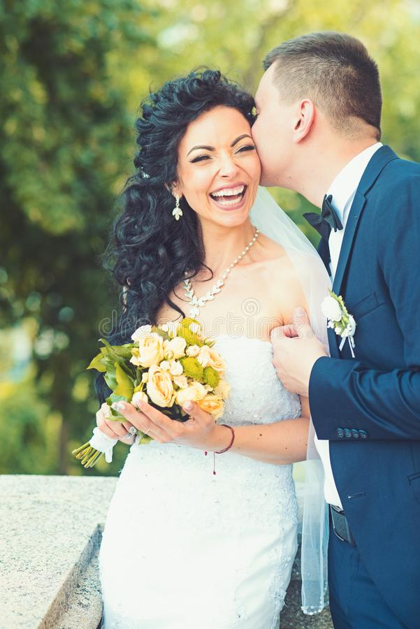 Sposa felice di bacio dello sposo con il mazzo Sorriso dell'uomo e della donna sul giorno delle nozze Coppie di nozze nell'amore  immagini stock