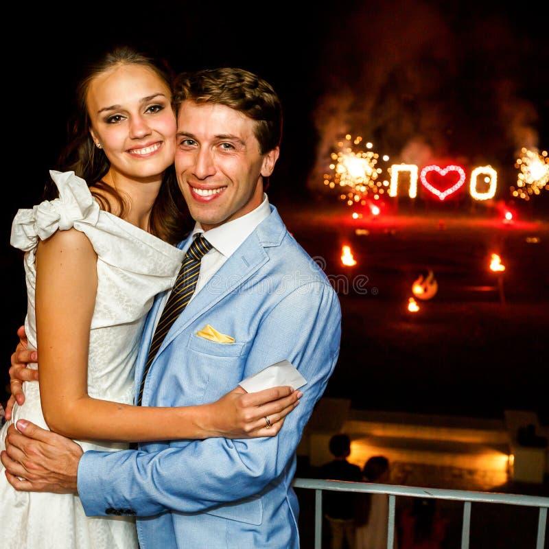 Sposa felice e sposo che abbracciano sorridere sul fuoco d'artificio del fondo fotografia stock