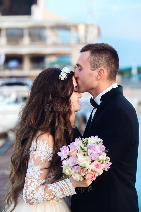 Sposa felice e sposo che baciano vicino all'yacht sulla spiaggia fotografia stock libera da diritti
