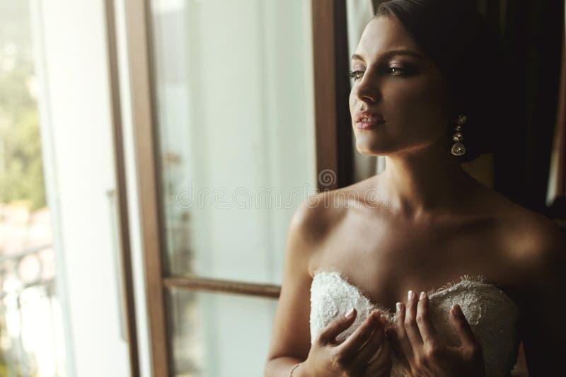 Sposa francese esotica splendida in vestito bianco che posa vicino alla finestra c immagine stock libera da diritti