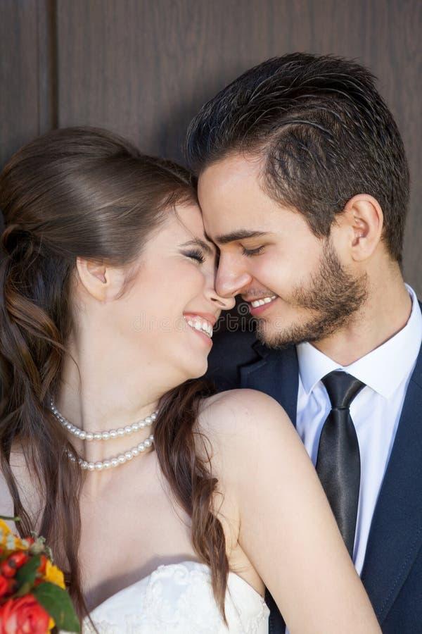 Sposa giovane di risata e sposo felice che la esaminano fotografia stock libera da diritti