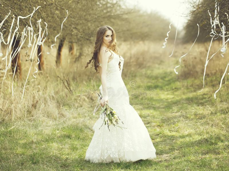 Sposa graziosa all'aperto Bella giovane sposa in vestito da sposa bianco con i fiori nel campo con i nastri sugli alberi all'aper fotografia stock libera da diritti