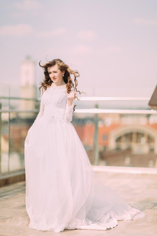 Sposa graziosa con capelli ricci lunghi in vestito da sposa che posa sul terrazzo fotografia stock libera da diritti