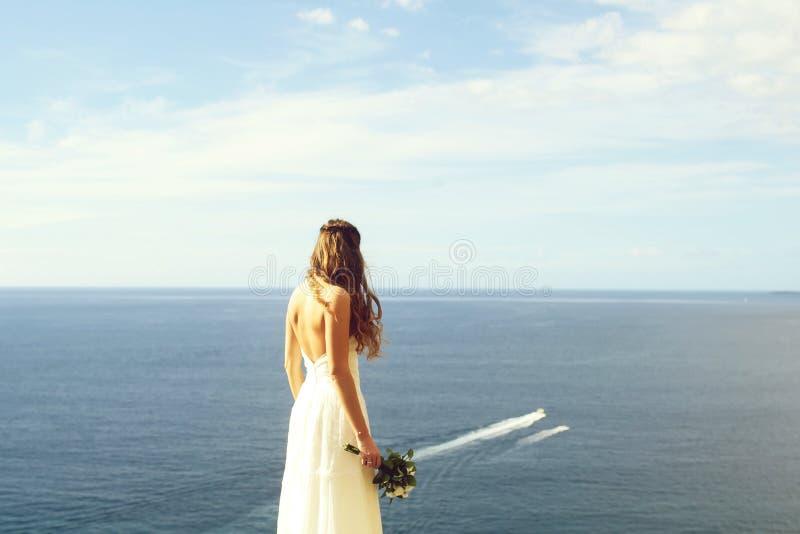Sposa graziosa in vestito bianco con il mazzo di nozze fotografia stock libera da diritti
