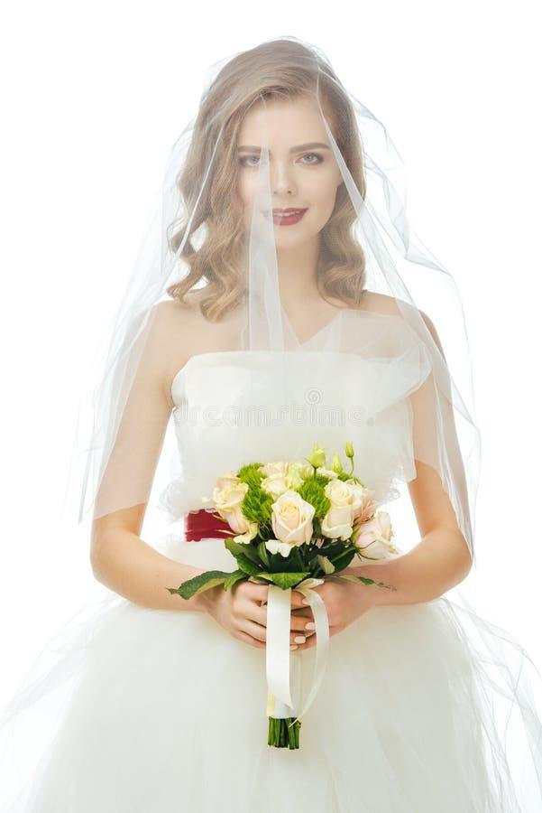 Sposa graziosa in vestito da sposa e velo con il mazzo di nozze in mani isolate su bianco fotografie stock